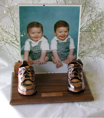 Bronzed shoes on walnut base with clear frame