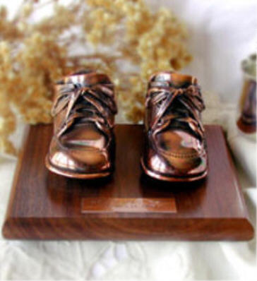Bronzed shoes on walnut base