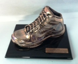 Adult shoes. Adult shoe bronzed and mounted on black lacquer base.